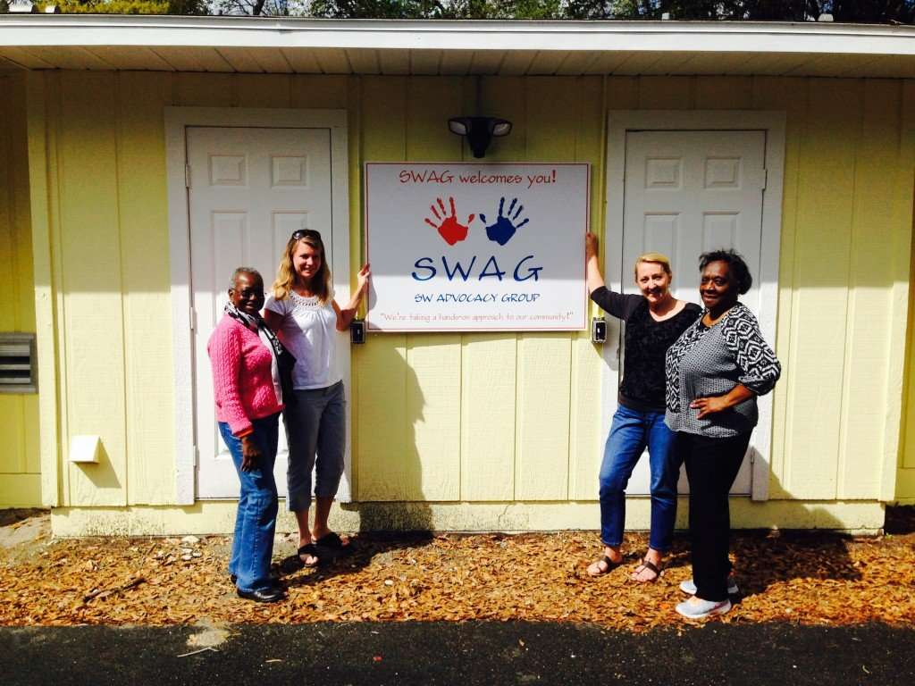 SWAG board members standing next to a SWAG sign welcoming visitors to the SW Health Clinic
