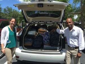 Megan and Pedro loading backpacks at Tower Hill Insurance Group