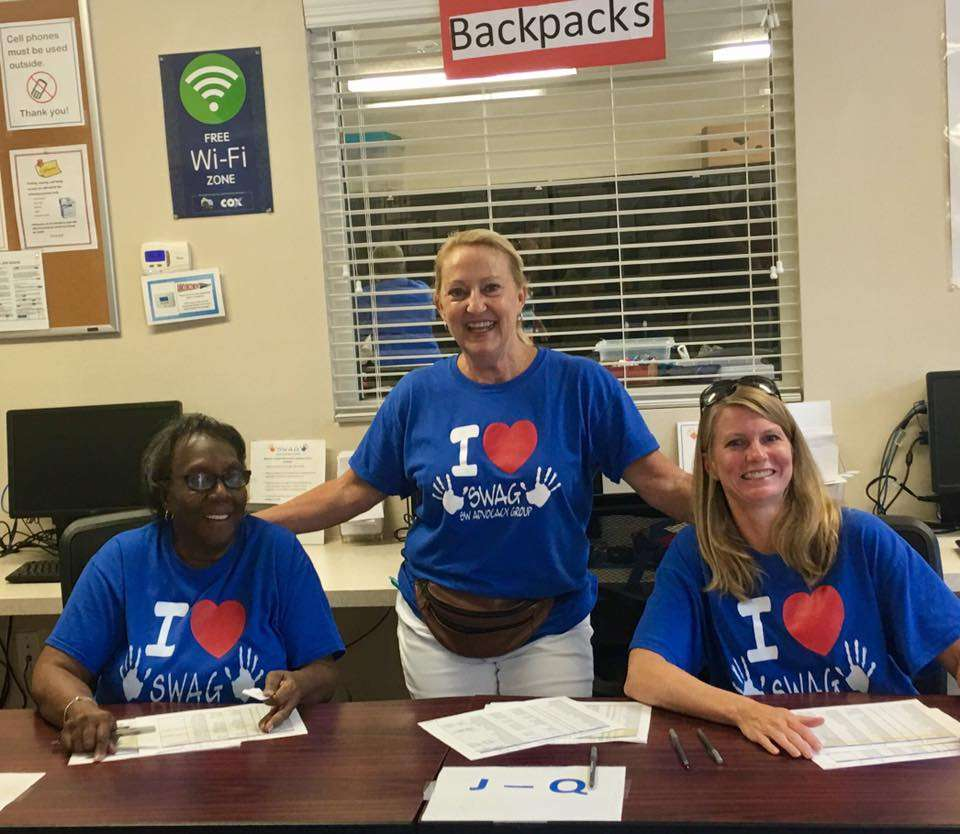Three SWAG leaders smiling and working together inside the SWAG Family Resource Center