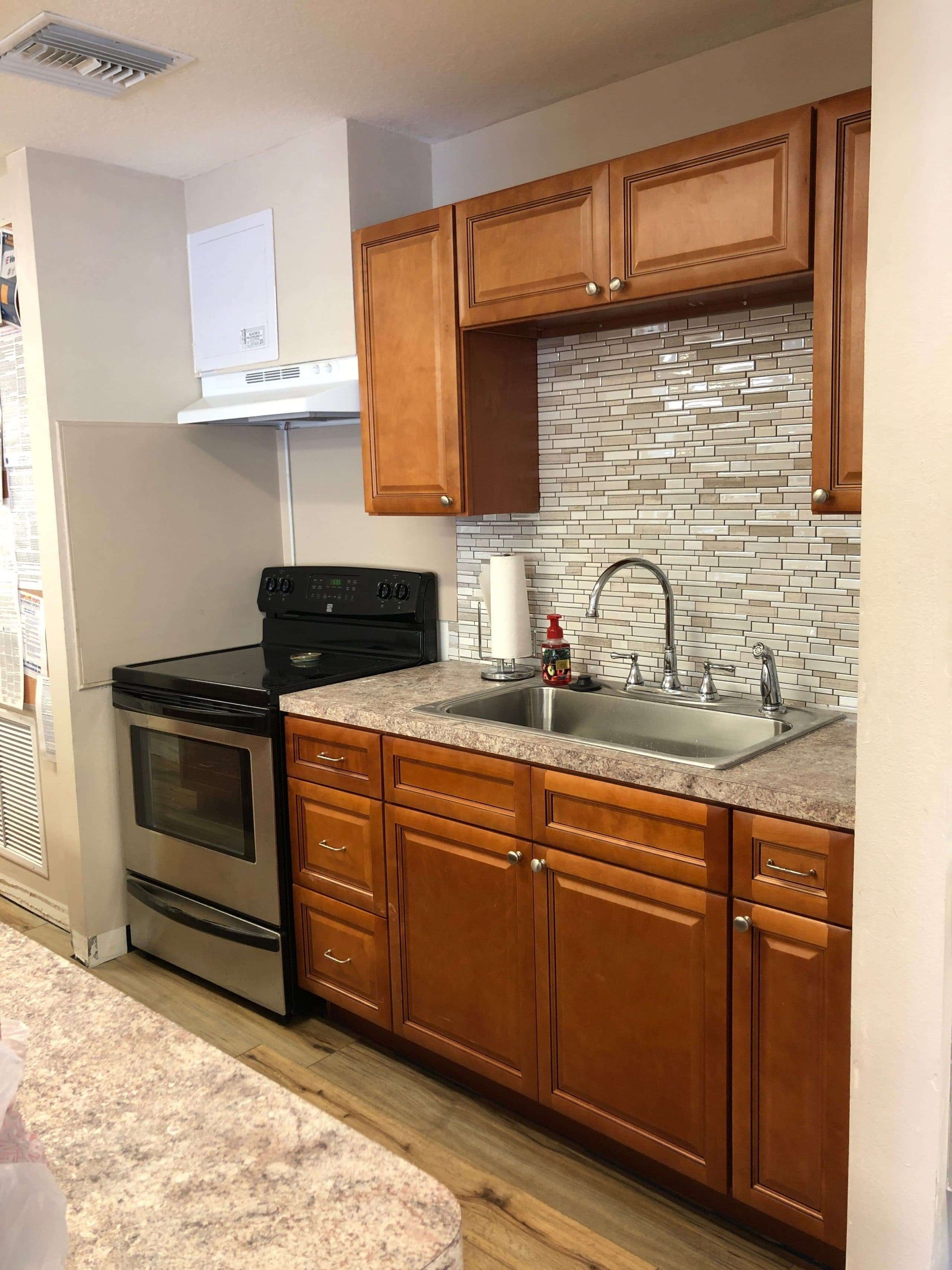 The kitchen in the Family Resource Center, including an oven, a large sink, and overhead cabinets