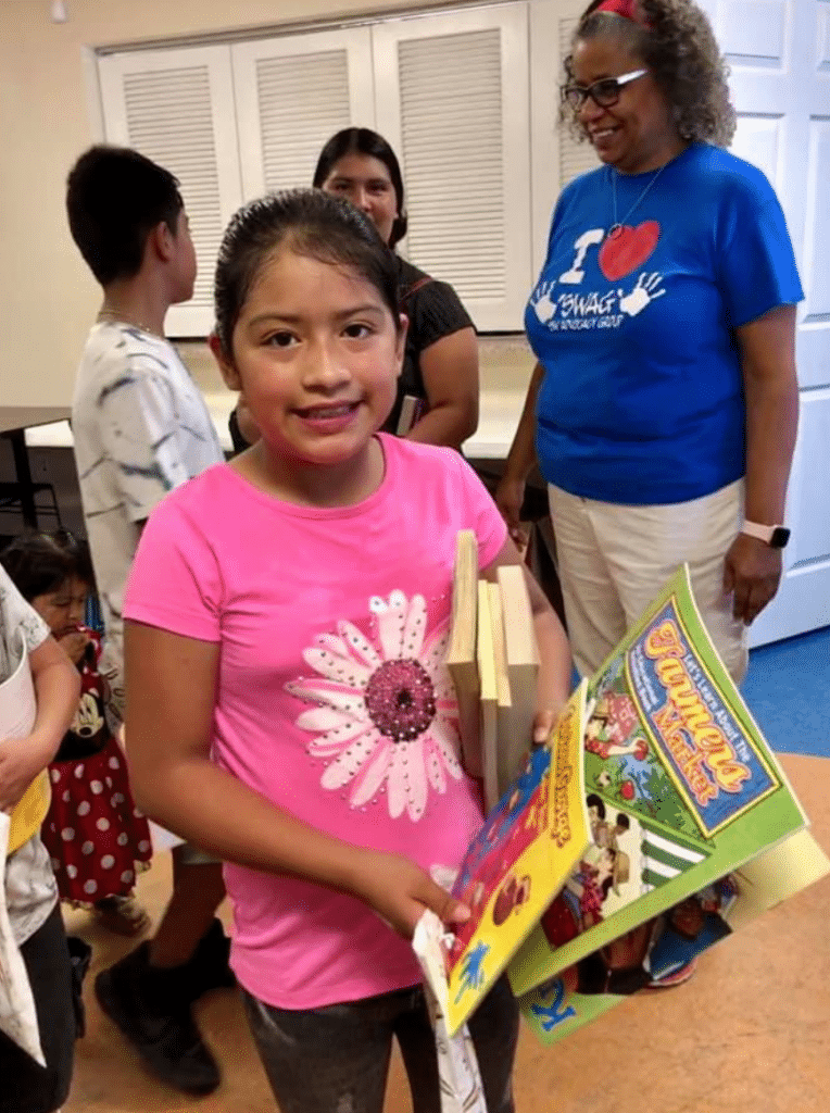 A child carrying a stack of four books under her arms and three colorful activity books in her hands