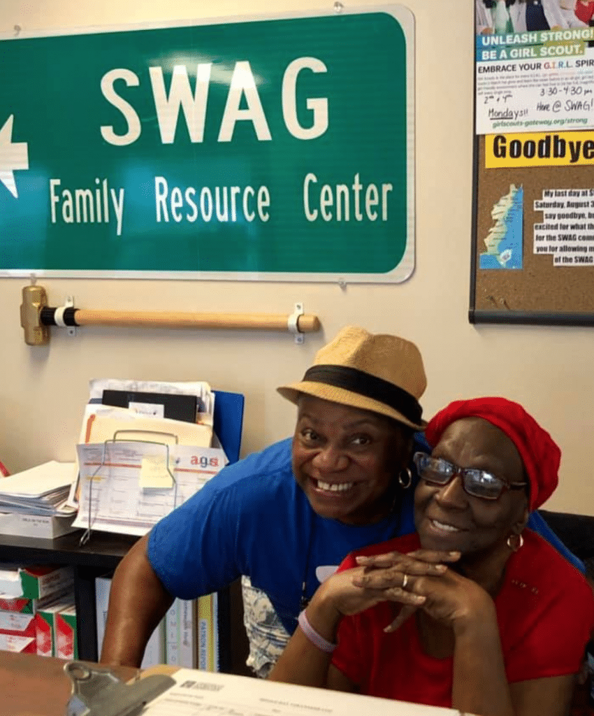 Two SWAG board members sitting behind the front desk of the SWAG Family Resource Center