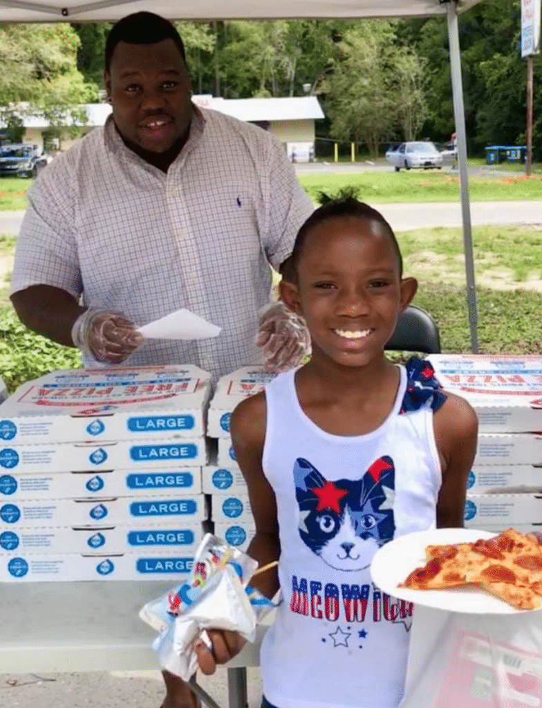 A child carrying a paper plate with pizza and a juice box, having just been served by an adult at an outdoor event
