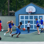 Four children playing basketball on the FRC playground with four adults in SWAG tee shirts