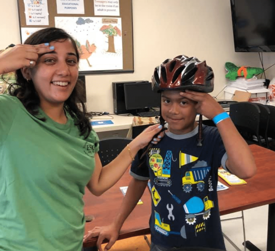 A child and a SWAG volunteer demonstrating the two-finger rule for wearing bike helmets safely