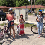 Six children and youth wearing helmets and standing next to new bikes