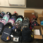 34 new backpacks sitting next to 7 boxes of new school supplies