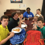 Five children and two adults sitting around a table in the SWAG Family Resource Center eating pizza and holding new backpacks