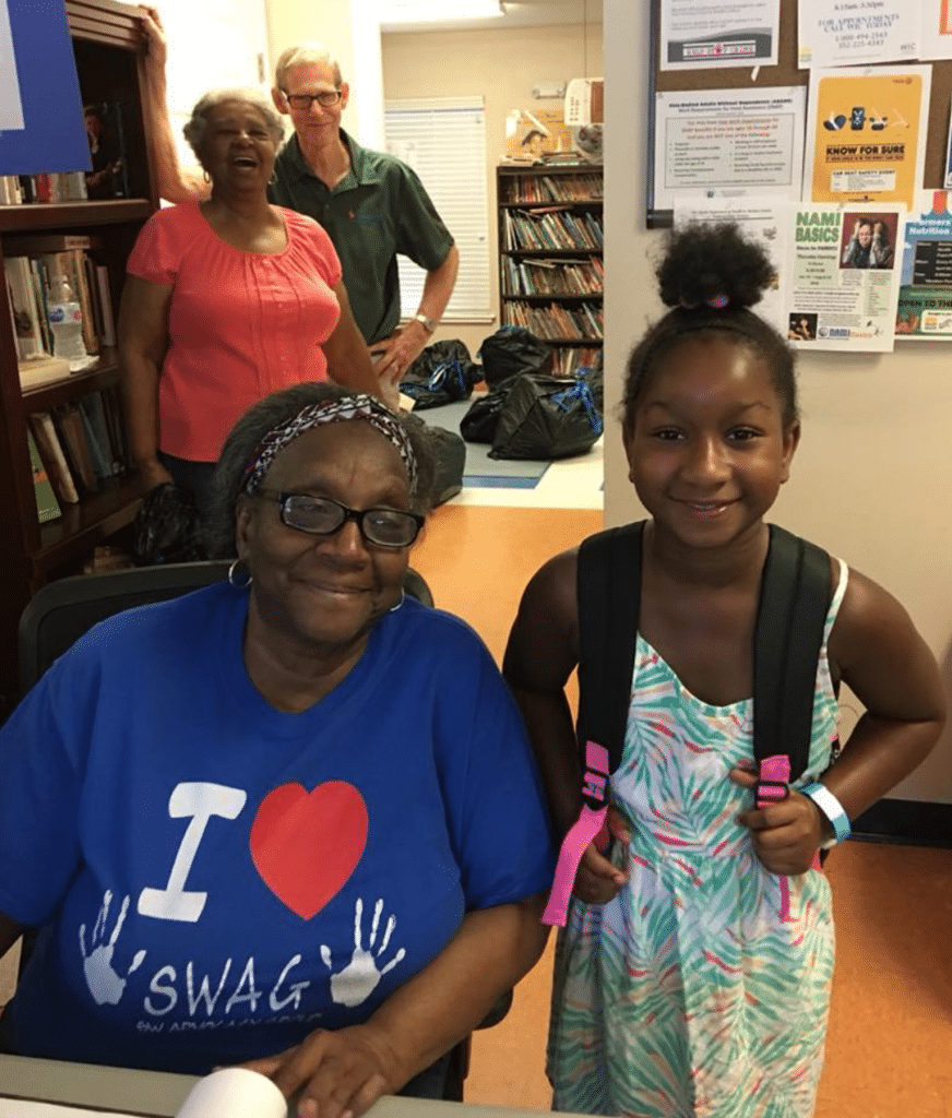 Joan in the SWAG Family Resource Center with a child smiling and wearing a backpack