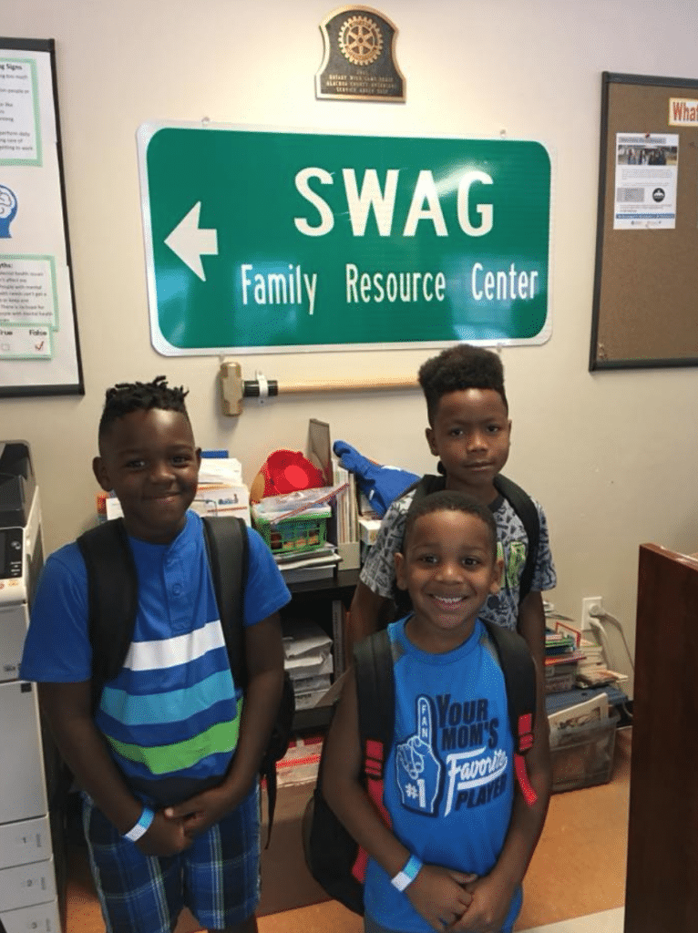 Three children smiling and wearing backpacks in front of a SWAG Family Resource Center sign