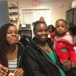 A teen and an adult carrying a young child smiling for the camera during an event inside the SWAG Family Resource Center
