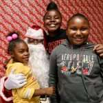 Three smiling children posing with Santa Claus during a Christmas event at the SWAG Family Resource Center