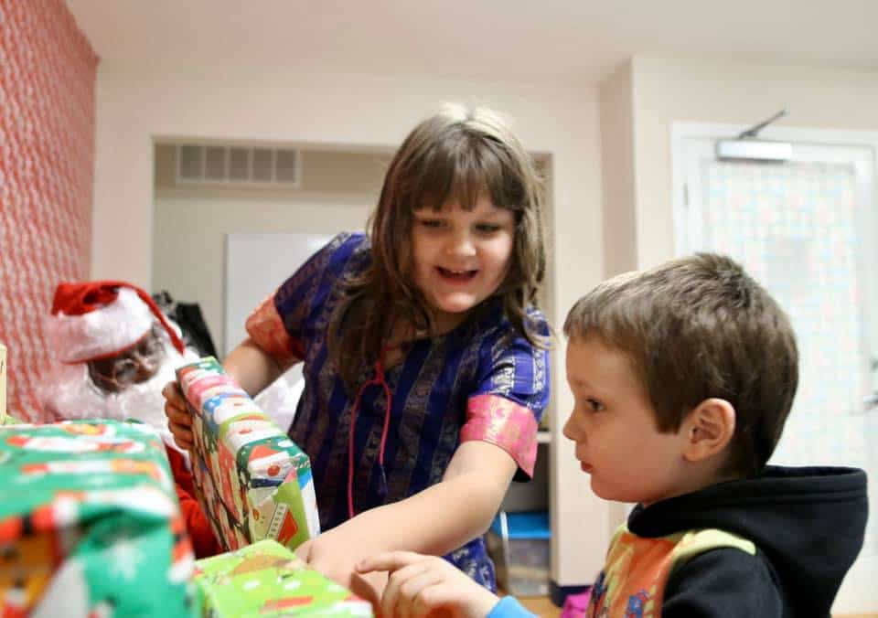 Two children excitedly looking at a stack of gift-wrapped boxes during a Christmas event at the SWAG Family Resource Center