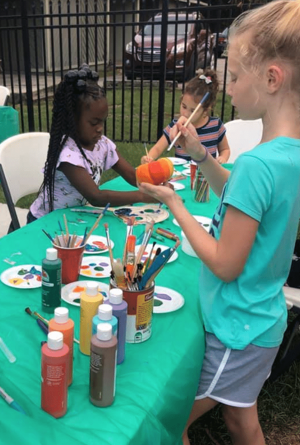 Three children painting pumpkins at a craft table during an outdoor event at the SWAG Family Resource Center