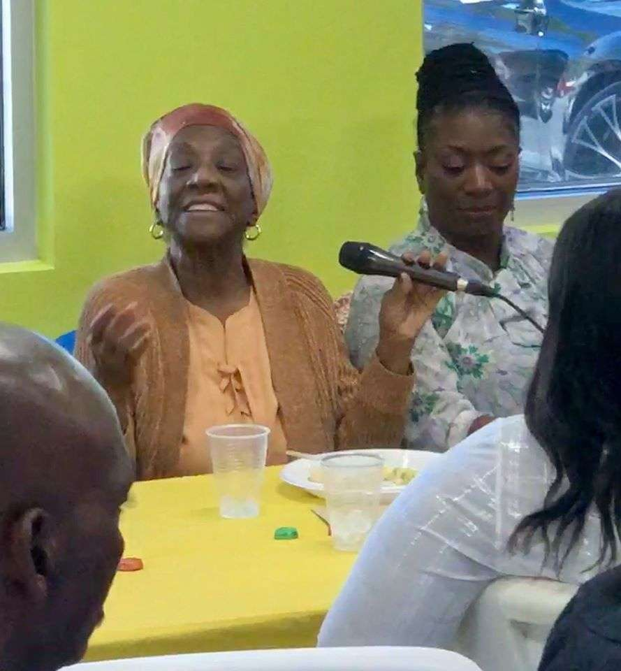 Joan Canton speaking into a microphone during a playground naming ceremony in her honor