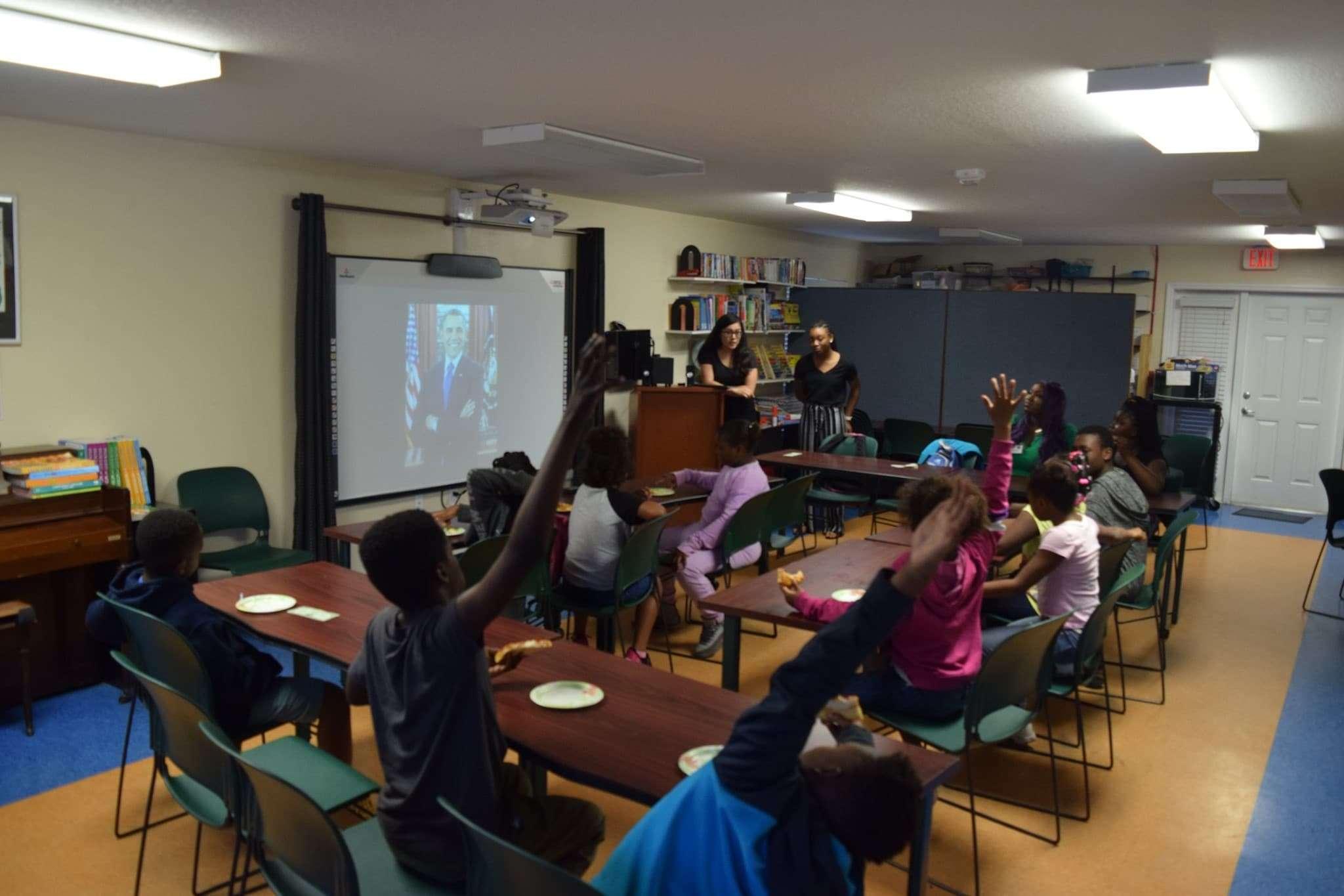 Children raising their hands from their seats during a children's program inside the FRC