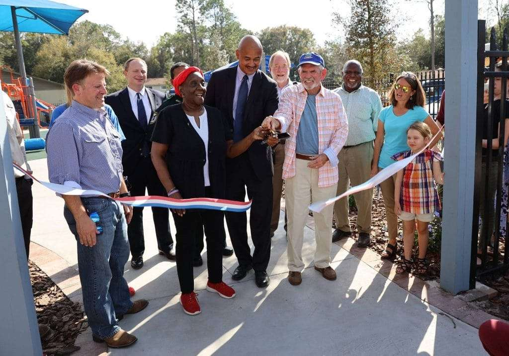 A group of people smiling while cutting the ribbon for the SWAG pocket park in the Linton Oaks community