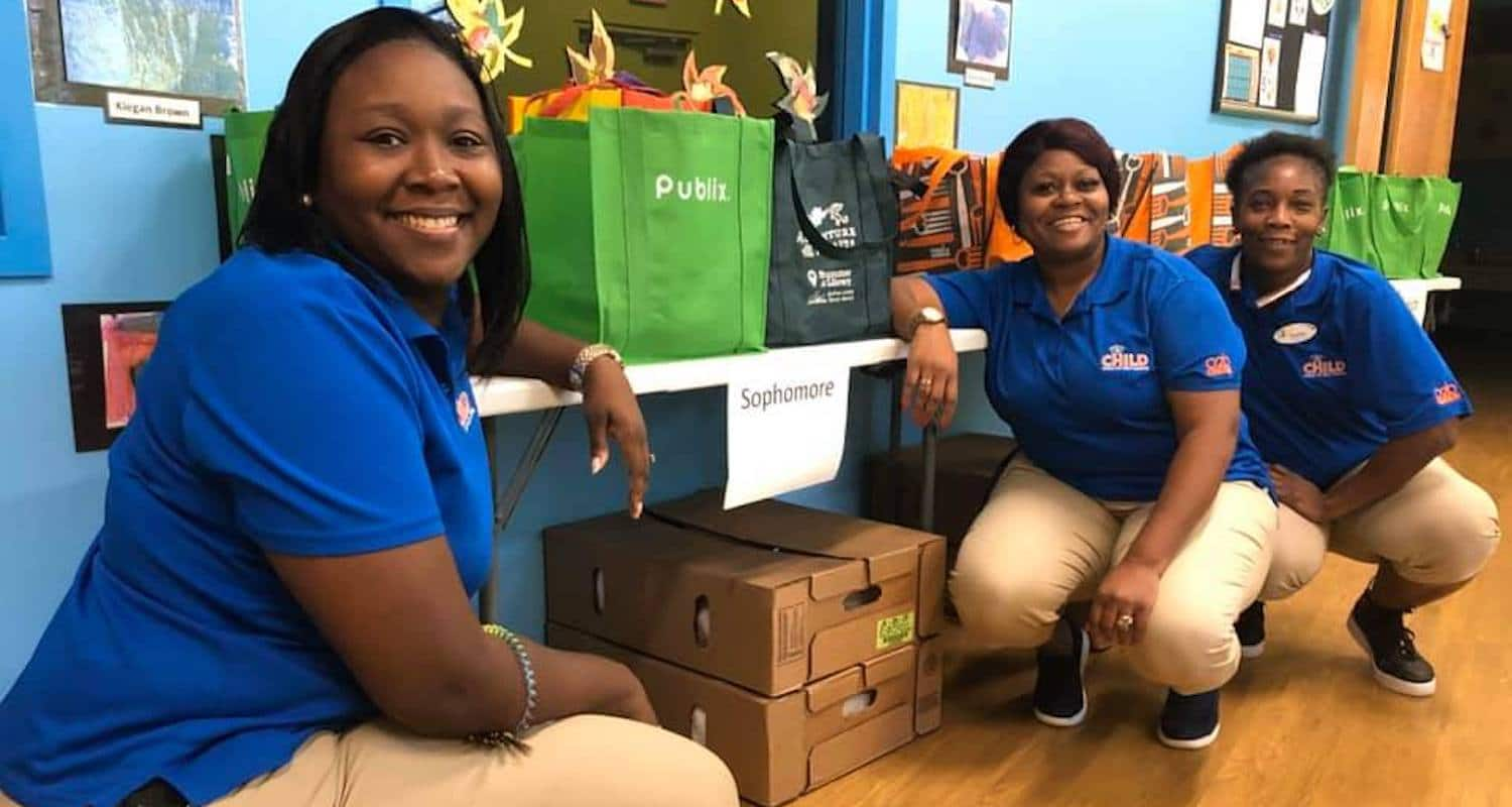 Three CHILD Center staff smiling and crouching next to several tables covered with canvas bags filled with food