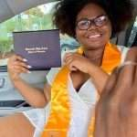 Kasie-Lynn Kimbrough wearing graduation regalia and holding a Gainesville High School diploma