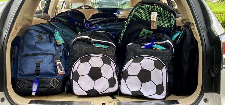 An open car trunk filled with children's backpacks from Tower Hill Insurance