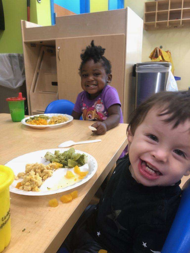 Two smiling children seated at a table in front of plates of food
