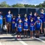 Eight children and four summer session counselors wearing SWAG tee shirts and standing in front of a large van