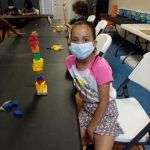 A SWAG summer session participant sitting at a table next to a tall tower made from colorful wooden building blocks