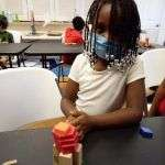 A child sitting at a table in the SWAG Family Resource Center next to a tower of wooden building blocks