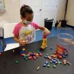 A child in the process of building a tall tower with colorful wooden building blocks