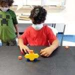 Two children wearing masks and observing a construction made from colorful wooden building blocks of various shapes