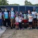 Six children and six summer session counselors wearing tie-dyed tee shirts and standing in front of a large van