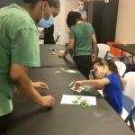 A SWAG summer session counselor helping a child with a craft project in the SWAG Family Resource Center
