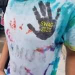 """A person wearing a tie-dyed tee shirt with a handprint and text that reads """"SWAG 2020"""""""