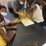 Three children and a summer camp counselor working on a craft project using dry spaghetti noodles