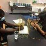 Four SWAG summer session participants working on a craft project using dry spaghetti noodles