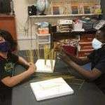 Two SWAG summer session participants wearing masks and working on a craft project together