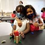 Two young children wearing masks and standing next to each other behind a tower built with wooden blocks