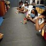 Six children building with wooden blocks of various shapes in the SWAG Family Resource Center