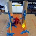 A mechanical contraption build from paper towel rolls, pencils, masking tape, string, and an apple