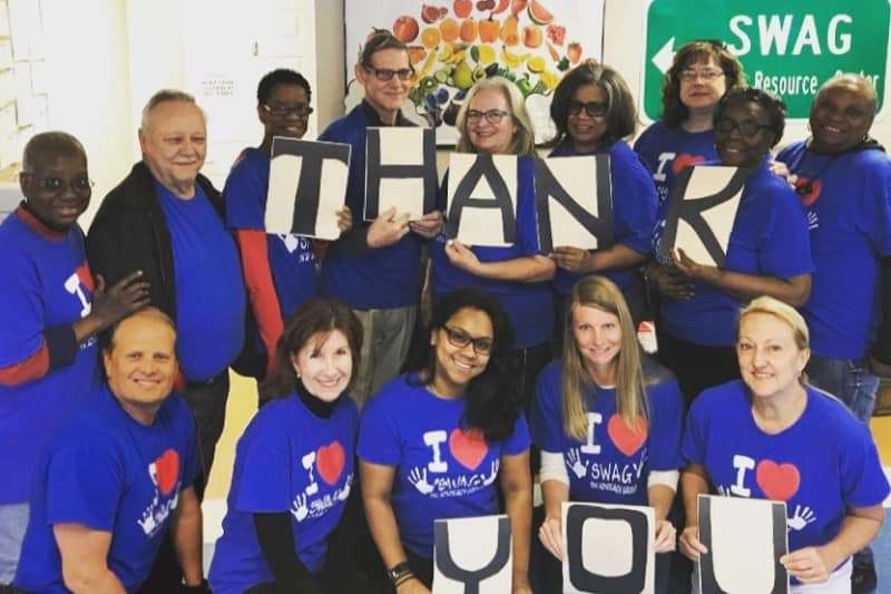 """Fourteen SWAG board members in """"I love SWAG"""" shirts holding the letters of the words """"thank you"""" for Amazing Give donors"""