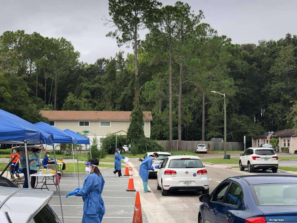 A line of cars parked alongside a row of tents serving drive-through customers at the free COVID-19 testing clinic
