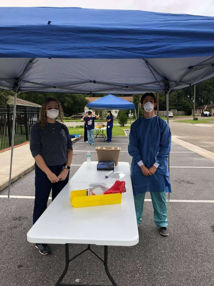 Two community partners wearing masks and standing under a tent at SWAG's free COVID-19 testing clinic