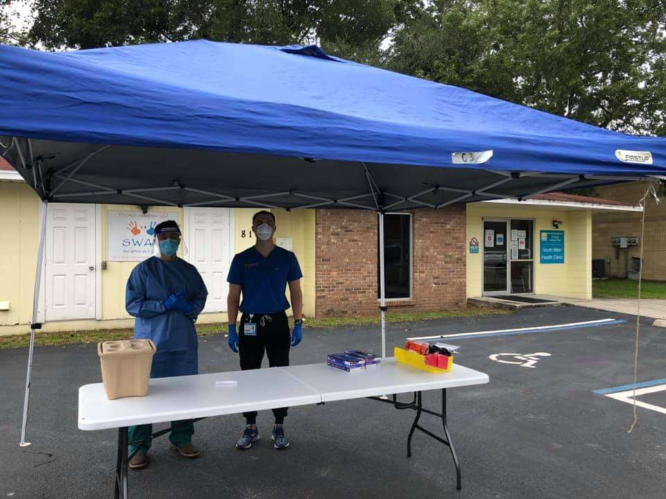Two community partners wearing masks and medical clothing and standing under a tent in front of the Southwest Health Clinic