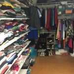 The inside of the clothing closet at the SWAG Family Resource Center, with clothes folded on shelves and hanging on hangers