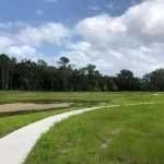The new walking trail near the Linton Oaks neighborhood featuring a smooth, paved walkway surrounded by grass and trees