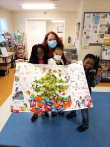 Three SWAG after school kids present staff member Robin with a giant holiday card featuring a tree decorated with real candy