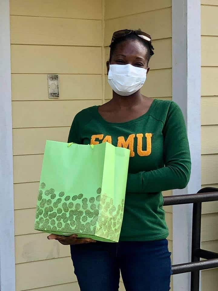 Kristy Goldwire wearing a face mask and FAMU tee shirt and holding a gift bag outside the SWAG Family Resource Center