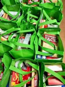 A close-up view of several tote bags stuffed with food for Thanksgiving 2020