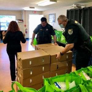 Alachua County Sherriff's Office members open boxes of food to distribute to the SWAG community