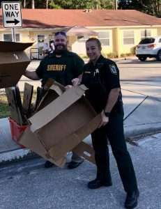 Two members of the Alachua County Sherriff's Office unloading boxes of food from a truck.